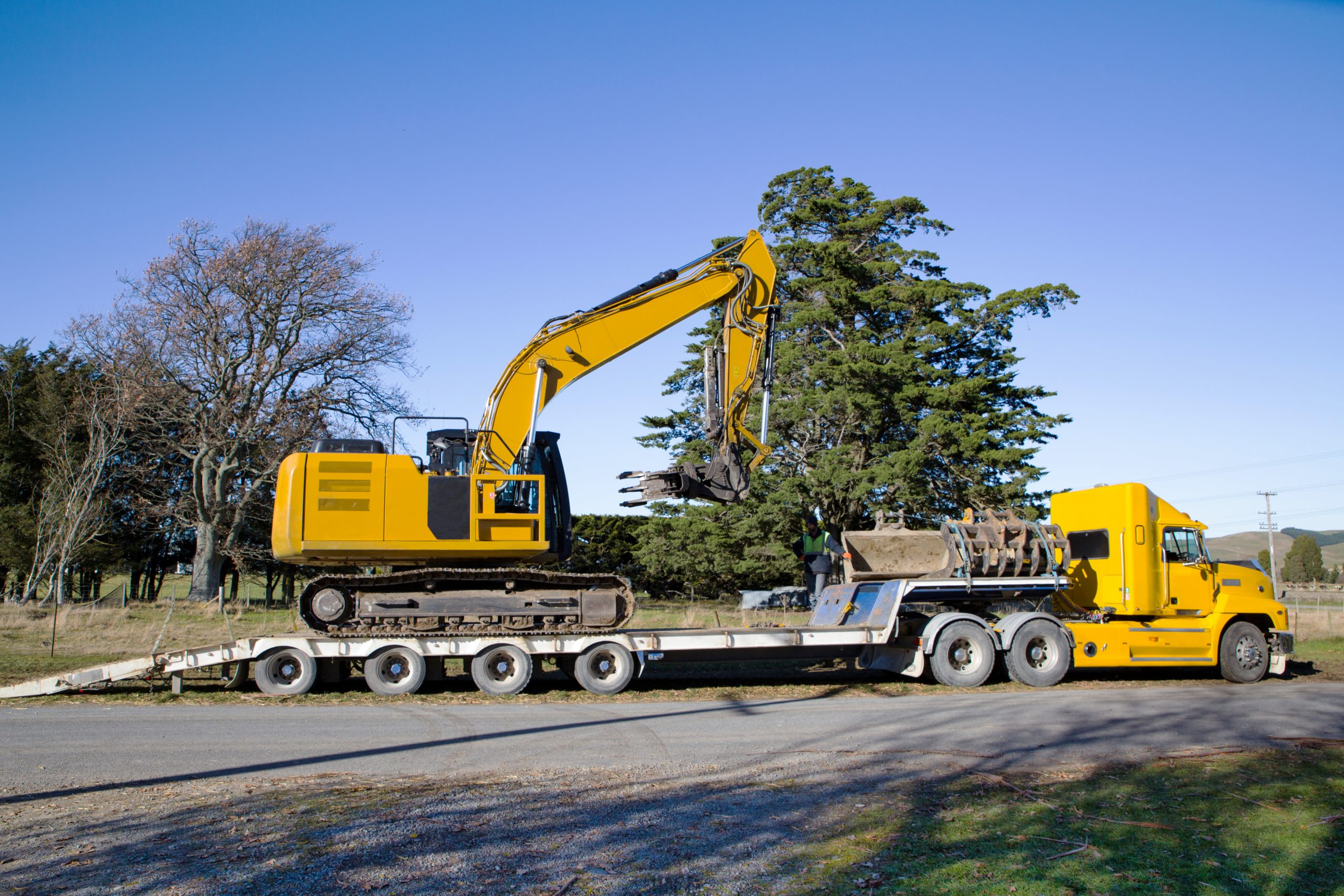 A large yellow digger is delivered to a worksite by a truck and tailer unit in Canterbury, New Zealand